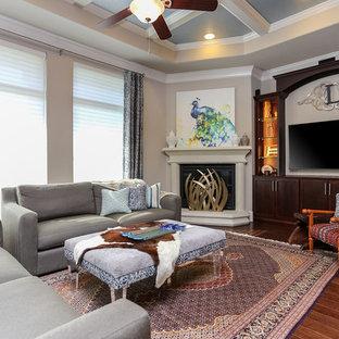 ヒューストンの中サイズのトラディショナルスタイルのおしゃれなファミリールーム (ベージュの壁、無垢フローリング、コーナー設置型暖炉、漆喰の暖炉まわり、埋込式メディアウォール) の写真