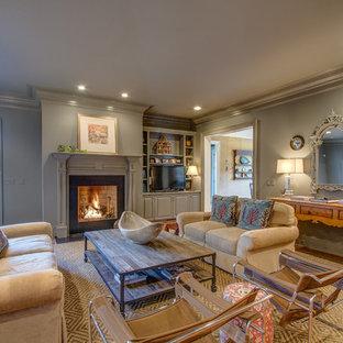 Immagine di un grande soggiorno chic chiuso con pareti grigie, parquet scuro, camino classico, cornice del camino in legno e porta TV ad angolo