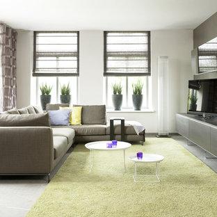 Foto di un soggiorno minimalista con TV autoportante e pavimento grigio