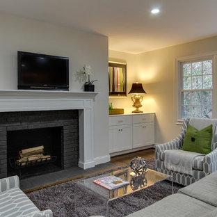 ローリーの中サイズのトランジショナルスタイルのおしゃれなファミリールーム (白い壁、濃色無垢フローリング、標準型暖炉、レンガの暖炉まわり、壁掛け型テレビ) の写真