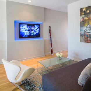 Modelo de sala de estar abierta, moderna, pequeña, con paredes blancas, suelo de madera en tonos medios y televisor colgado en la pared
