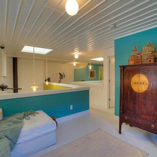 Esempio di un piccolo soggiorno industriale stile loft con pareti blu, moquette e TV nascosta