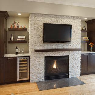 Foto de sala de estar con barra de bar tradicional renovada, pequeña, con paredes grises, suelo de madera clara, marco de chimenea de piedra y televisor colgado en la pared