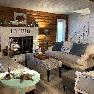 他の地域の中サイズのビーチスタイルのおしゃれなファミリールーム (白い壁、ラミネートの床、標準型暖炉、石材の暖炉まわり、壁掛け型テレビ、グレーの床) の写真
