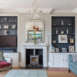 Imagen de sala de estar tradicional, de tamaño medio, con paredes grises, suelo de madera en tonos medios, estufa de leña y pared multimedia
