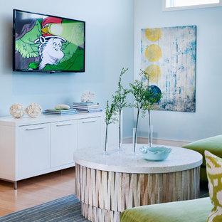 ニューヨークの大きいビーチスタイルのおしゃれなファミリールーム (青い壁、竹フローリング、コーナー設置型暖炉、金属の暖炉まわり、壁掛け型テレビ、ベージュの床) の写真