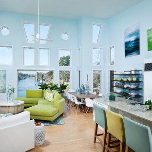 ニューヨークの広いビーチスタイルのおしゃれなロフトリビング (青い壁、竹フローリング、コーナー設置型暖炉、金属の暖炉まわり、壁掛け型テレビ、ベージュの床) の写真