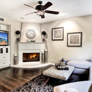 ロサンゼルスの大きいコンテンポラリースタイルのおしゃれなファミリールーム (ベージュの壁、無垢フローリング、コーナー設置型暖炉、漆喰の暖炉まわり、壁掛け型テレビ、茶色い床) の写真
