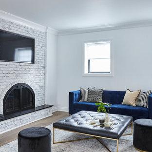 ニューヨークの中サイズのコンテンポラリースタイルのおしゃれなオープンリビング (白い壁、標準型暖炉、レンガの暖炉まわり、埋込式メディアウォール、グレーの床) の写真