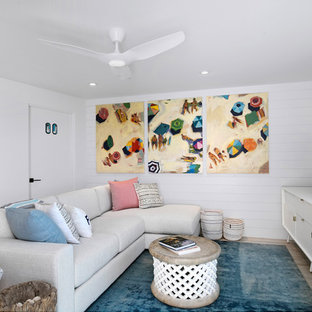 Design ideas for a small beach style open concept family room in Tampa with white walls, beige floor and a freestanding tv.