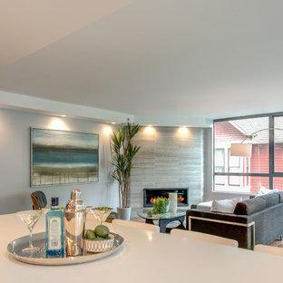 バンクーバーの中サイズのトロピカルスタイルのおしゃれなファミリールーム (青い壁、無垢フローリング、コーナー設置型暖炉、タイルの暖炉まわり、テレビなし) の写真