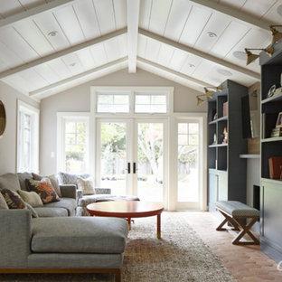 サンフランシスコの小さいラスティックスタイルのおしゃれなオープンリビング (グレーの壁、テラコッタタイルの床、標準型暖炉、タイルの暖炉まわり、壁掛け型テレビ) の写真