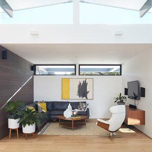 Modelo de sala de estar abierta, vintage, sin chimenea, con paredes blancas, suelo de madera clara y televisor colgado en la pared