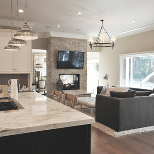 Inspiration for a mid-sized transitional open concept family room in San Francisco with beige walls, medium hardwood floors, a two-sided fireplace, a stone fireplace surround, a wall-mounted tv and brown floor.
