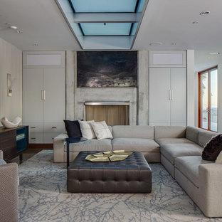 サンフランシスコの大きいモダンスタイルのおしゃれなファミリールーム (標準型暖炉、コンクリートの暖炉まわり、壁掛け型テレビ、白い壁、茶色い床) の写真