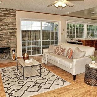 Foto de sala de estar abierta, tradicional, pequeña, con paredes beige, suelo de madera clara, chimenea de esquina y marco de chimenea de piedra