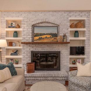アトランタの中サイズのビーチスタイルのおしゃれなファミリールーム (ベージュの壁、濃色無垢フローリング、標準型暖炉、レンガの暖炉まわり、据え置き型テレビ、青い床) の写真