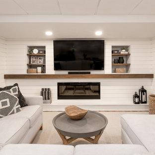 Esempio di un soggiorno classico di medie dimensioni e chiuso con pareti bianche, pavimento in laminato, camino sospeso, cornice del camino in legno, TV a parete e pavimento marrone