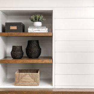 ミルウォーキーの中サイズのトラディショナルスタイルのおしゃれな独立型ファミリールーム (白い壁、ラミネートの床、吊り下げ式暖炉、木材の暖炉まわり、壁掛け型テレビ、茶色い床) の写真