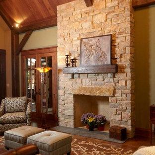 シカゴの中サイズのおしゃれなファミリールーム (黄色い壁、濃色無垢フローリング、標準型暖炉、石材の暖炉まわり、テレビなし) の写真