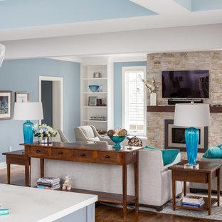 トロントの中サイズのコンテンポラリースタイルのおしゃれなファミリールーム (青い壁、無垢フローリング、標準型暖炉、コンクリートの暖炉まわり、壁掛け型テレビ) の写真
