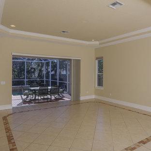 タンパの大きい地中海スタイルのおしゃれなファミリールーム (ベージュの壁、セラミックタイルの床、暖炉なし、壁掛け型テレビ、ベージュの床) の写真
