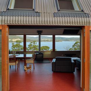 Réalisation d'une petite salle de séjour design fermée avec un mur gris, un sol en linoléum, une cheminée standard, un manteau de cheminée en carrelage, un téléviseur encastré et un sol rouge.