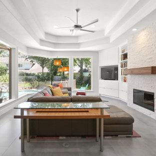 ヒューストンの中くらいのコンテンポラリースタイルのおしゃれなオープンリビング (ライブラリー、グレーの壁、セラミックタイルの床、標準型暖炉、積石の暖炉まわり、埋込式メディアウォール、グレーの床、折り上げ天井) の写真