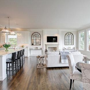 Foto de sala de estar abierta, de estilo de casa de campo, con paredes blancas, suelo de madera en tonos medios, chimenea tradicional, marco de chimenea de yeso y televisor colgado en la pared
