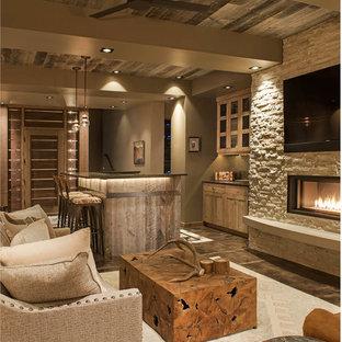 Foto på ett stort rustikt allrum med öppen planlösning, med en hemmabar, en bred öppen spis, en spiselkrans i sten, en väggmonterad TV, grå väggar, mörkt trägolv och brunt golv