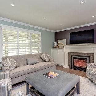 トロントの中サイズのトラディショナルスタイルのおしゃれな独立型ファミリールーム (マルチカラーの壁、無垢フローリング、標準型暖炉、タイルの暖炉まわり、壁掛け型テレビ、茶色い床) の写真
