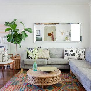 Imagen de sala de estar abierta, vintage, pequeña, con paredes blancas y suelo de madera en tonos medios