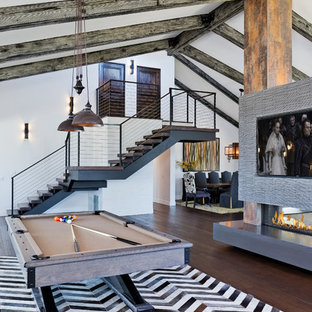Example of a huge trendy family room design in Los Angeles with a hanging fireplace and a media wall