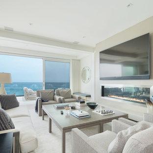 ロサンゼルスの中くらいのビーチスタイルのおしゃれなオープンリビング (白い壁、カーペット敷き、横長型暖炉、金属の暖炉まわり、壁掛け型テレビ、白い床) の写真