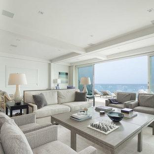 ロサンゼルスの中サイズのビーチスタイルのおしゃれなファミリールーム (白い壁、カーペット敷き、横長型暖炉、壁掛け型テレビ、白い床) の写真