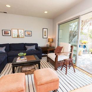 ロサンゼルスの小さいビーチスタイルのおしゃれなファミリールーム (グレーの壁、淡色無垢フローリング、標準型暖炉、石材の暖炉まわり、コーナー型テレビ) の写真