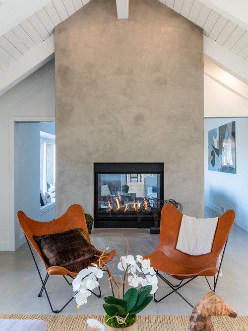 Salle de séjour avec un manteau de cheminée en béton et un sol en ...