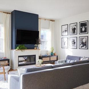 Foto de sala de estar abierta, marinera, con paredes blancas, suelo de madera en tonos medios, chimenea lineal y televisor colgado en la pared