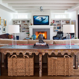 Design ideas for a beach style family room in Los Angeles with white walls, medium hardwood floors, a standard fireplace, a stone fireplace surround and a wall-mounted tv.