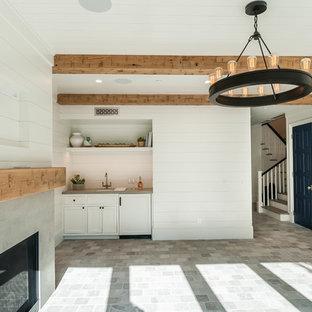 Diseño de sala de juegos en casa abierta, campestre, de tamaño medio, con paredes blancas, suelo de piedra caliza, chimenea tradicional, marco de chimenea de hormigón, televisor colgado en la pared y suelo gris