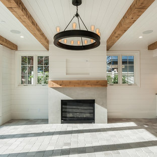 Modelo de sala de juegos en casa cerrada, de estilo de casa de campo, grande, con paredes blancas, suelo de piedra caliza, chimenea tradicional, marco de chimenea de hormigón y suelo gris