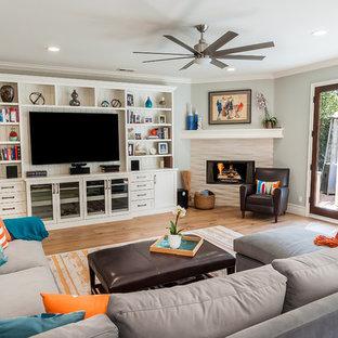 ロサンゼルスの大きいビーチスタイルのおしゃれなファミリールーム (グレーの壁、淡色無垢フローリング、コーナー設置型暖炉、石材の暖炉まわり、壁掛け型テレビ、マルチカラーの床) の写真