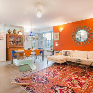 Exemple d'une salle de séjour tendance ouverte avec un mur orange et un sol en bois clair.