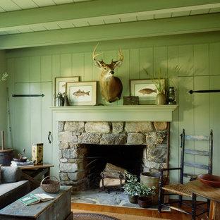 Idee per un piccolo soggiorno stile rurale chiuso con libreria, pareti verdi, parquet chiaro, camino classico, cornice del camino in pietra e TV nascosta