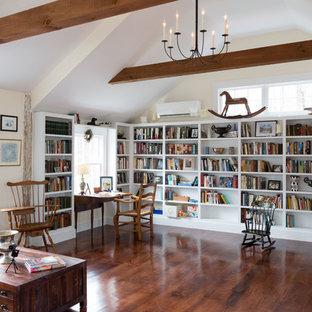 Foto de sala de estar con biblioteca abierta, campestre, grande, sin chimenea, con paredes beige, suelo marrón y suelo de madera oscura