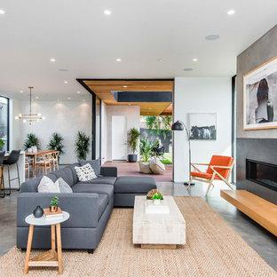 Idée de décoration pour une salle de séjour design ouverte avec un mur blanc, une cheminée ribbon, un manteau de cheminée en béton et un sol gris.