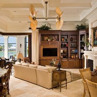 Modelo de sala de estar abierta, exótica, con paredes beige, chimenea tradicional y pared multimedia