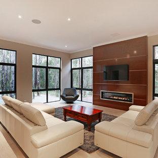 Idées déco pour une salle de séjour contemporaine ouverte avec un mur beige, un sol en bois clair, une cheminée ribbon, un manteau de cheminée en bois et un téléviseur fixé au mur.