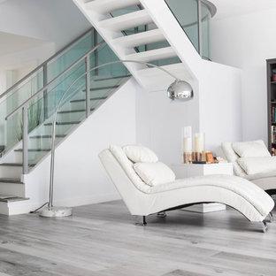 Imagen de sala de estar con biblioteca abierta, moderna, grande, con paredes blancas, suelo laminado y suelo multicolor
