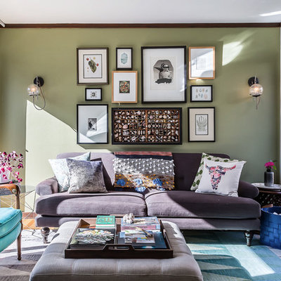 Example of a mid-sized eclectic enclosed medium tone wood floor and brown floor family room design in Denver with green walls and a wall-mounted tv